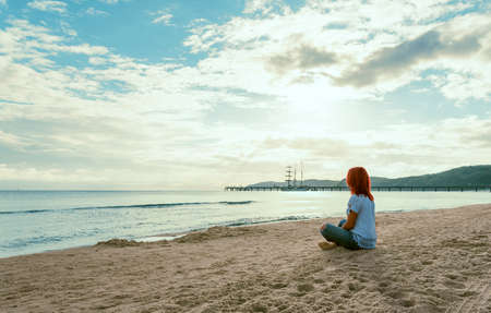 Summer scenery at Baltic Sea on Rugen island in Germany with a young woman sitting on the beach in the morning light.
