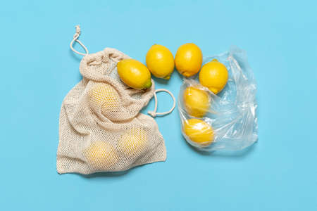 Replacing the plastic bag with the eco cotton bag. Bunch of lemons moving from one bag to another. Ethical consumerism with the new reusable cotton bag.