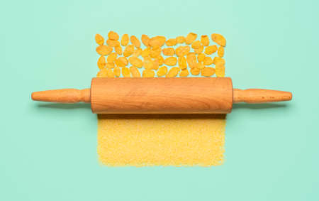 Above view with a rolling pin changing the maize flour into corn flakes. Healthy breakfast, corn cereals, isolated on a green-mint background.