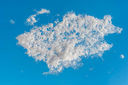 Snow on window glass, in winter, with a clear blue sky in background. Close-up, the texture of ice and snow on frozen glass. Winter weather concept.
