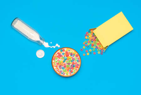 Above view with colorful cereals in a bowl and a bottle of milk isolated on a blue background. Messy breakfast table with spilled milk and cereals.