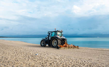 Morning beach scenery with tractor cleaning sand, at Baltic Sea, on Rugen Island, Germany. Getting beach ready for summer vacation. European travel.