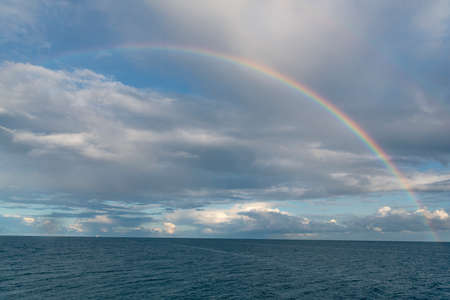 Seascape at Baltic sea with rainbow and cloudy sky. Summer scenery after rain from Rugen island, in Sassnitz, Germany. Imagens