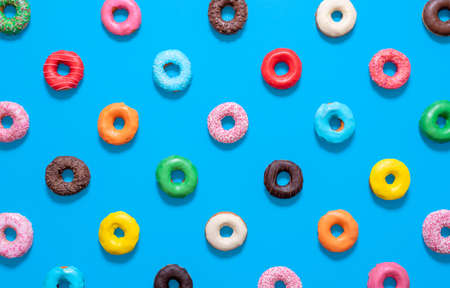 Flat lay with multicolored glazed doughnuts isolated on a blue background. Homemade chocolate doughnuts in different colors and styles.