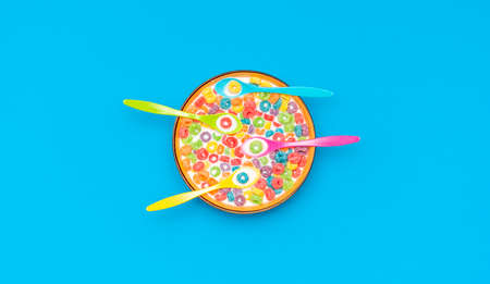 Top view with multicolored fruit rings cereals with milk in a bowl. Cereal bowl with four multicolored spoons isolated on a colored background.