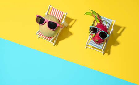 Above view with cantaloupe and dragon fruits sitting in miniature beach chairs with sunglasses on. Summer concept with exotic fruits sunbathing at the beach Stock Photo