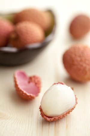 Lychees opened on a light wood table Stock Photo