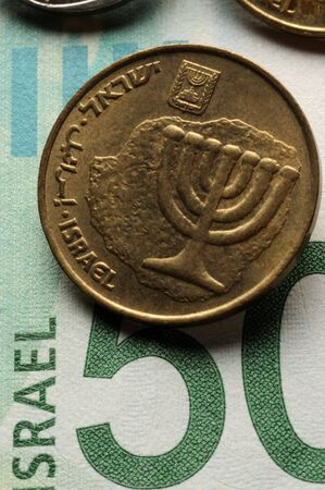 Close up of Israeli coins on banknote