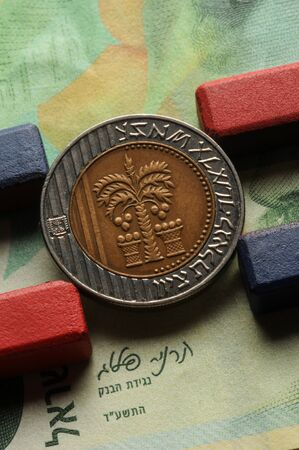 Israeli coin with magnets on banknote