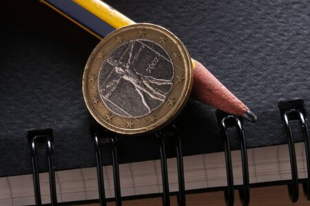 Italian euro with the Vitruvian man over a notebook with spiral and pencil 版權商用圖片