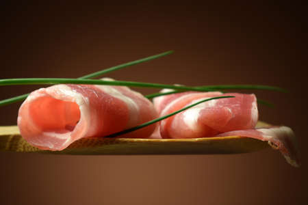 Pancetta slices with chives on spoon