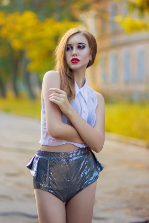Portrait of red-haired girl with bright makeup in shiny shorts and a white transparent blouse photo