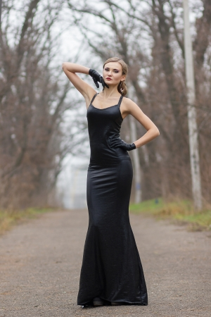 Portrait of a beautiful young woman with elegant hairstyle and bright make-up in a long black evening dress outdoors photo
