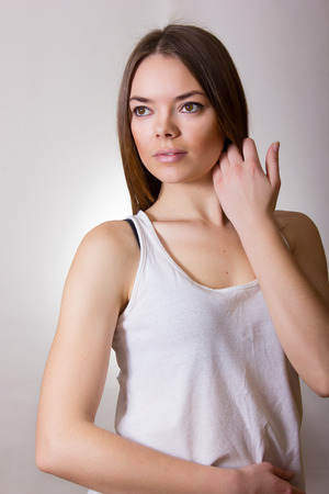 Portrait of a beautiful young woman in a white T-shirt with natural make-up and straight brown hair photo