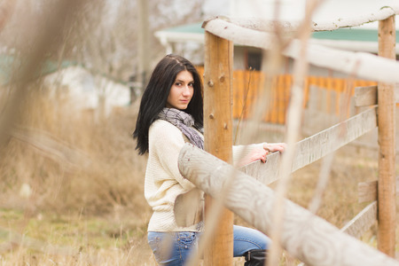 Outdoor portrait of young pretty beautiful woman in cold spring weather in park  Sensual brunette posing and having fun photo