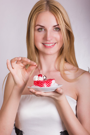 Portrait of a beautiful young blonde woman in the studio on a white background  Girl posing in a beautiful dress with a cake in the shape of heart  photo