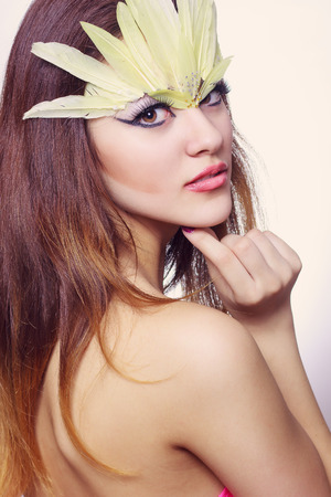 Portrait of beautiful young brown-haired woman with long hair in a studio  Makeup with long black arrow and yellow long feathers photo