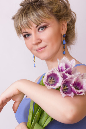 Portrait of a beautiful young blonde girl on a white background in a blue dress  Woman posing with a bouquet of purple tulips  photo