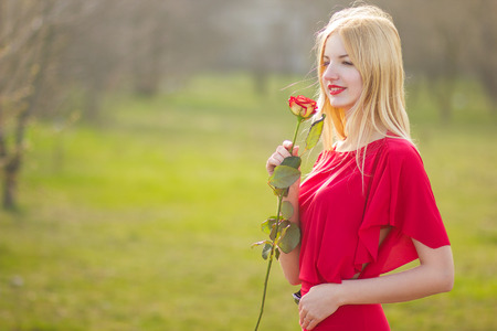 maxi dress: portrait of blond woman in red maxi dress outdoor