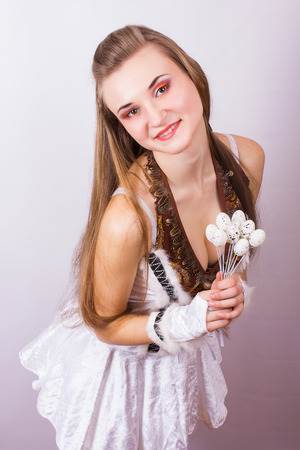 Portrait of beautiful young brown-haired woman with long hair  Girl dressed in costume posing with birds and quail eggs  photo