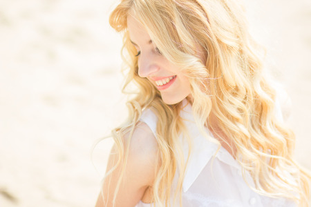 wavy hair: Portrait of a beautiful young blonde woman with wavy hair in nature  Girl posing on the beach, standing on the sand near the water Stock Photo