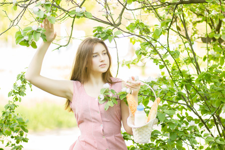Portrait of a beautiful young girl with brown hair in retro dress on nature  The woman gathered her basket on picnic photo