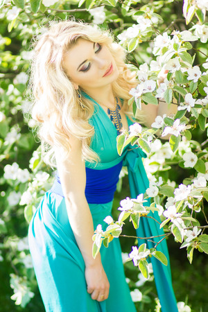 Portrait of a beautiful young blonde woman with long hair in a long blue dress with a high slit in nature  photo