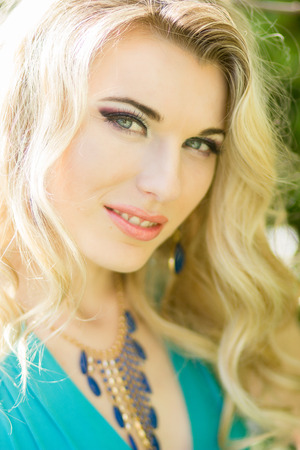 maxi dress: Portrait of a beautiful young blonde woman with long hair in a long blue dress with a high slit in nature  Stock Photo