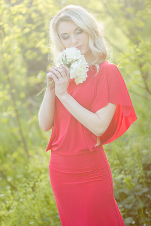 Portrait of a beautiful young blonde woman in the image of the bride  A girl wearing a red evening dress and in her hands she holds a bouquet of roses photo