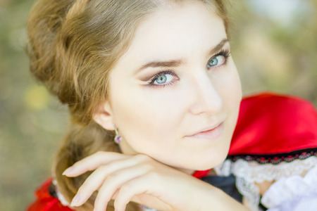 light brown hair: Portrait of a beautiful young woman in nature in the Little Red Riding Hood costume. Girl dressed as fairy-tale characters with beautiful make-up for Halloween