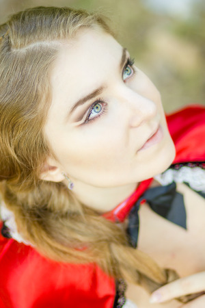 Portrait of a beautiful young woman in nature in the Little Red Riding Hood costume. Girl dressed as fairy-tale characters with beautiful make-up for Halloween