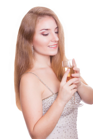 smiling woman in evening dress with glass of sparkling wine over white background photo