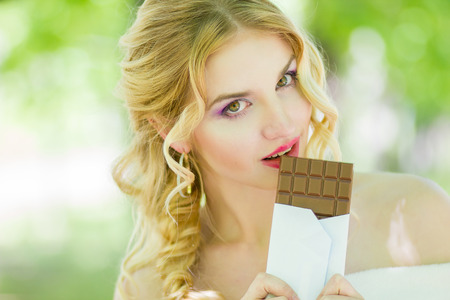 chocolate background: Portrait of a chocolate loving young blonde beauty on the background of trees in the park. Soft focus