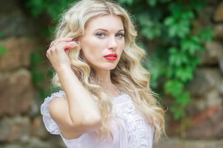 Portrait of a beautiful young blonde woman with long hair in a white dress on a background of a stone wall in nature. Soft focus Stock Photo