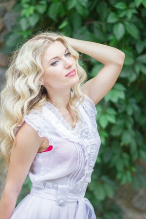 tight focus: Portrait of a beautiful young blonde woman with long hair in a white dress on a background of a stone wall in nature. Soft focus Stock Photo