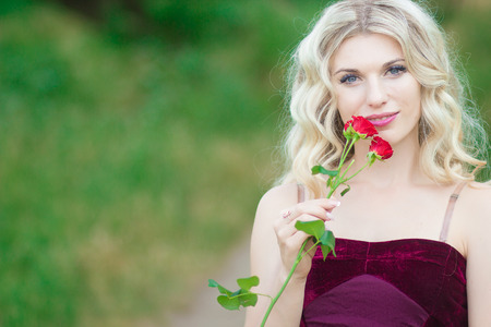 mujer con rosas: Beautiful young blonde woman with curly hair holding a basket full of red roses. Soft focus