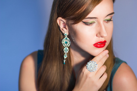silver hair: Elegant Posh Woman with Diamond Earrings And Ring. Platinum Jewelry with green And White Diamonds