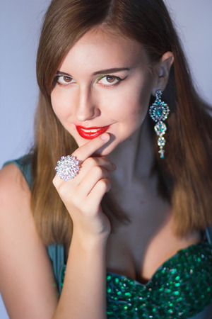 platinum hair: Elegant Posh Woman with Diamond Earrings And Ring. Platinum Jewelry with green And White Diamonds