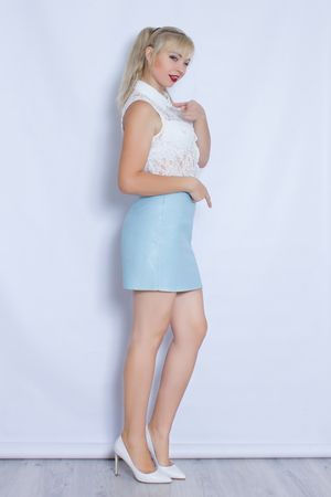 Portrait of a beautiful blonde girl in a blue skirt. A young woman stands full-length in high heeled shoes. Hair collected in the tail