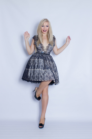 Young beautiful blonde in full growth, in a cocktail dress. Photo taken in the studio on a gray background. Girl with bright make-up, posing on camera
