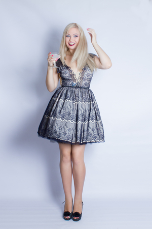 Portrait of a beautiful young blond woman in a beautiful cocktail dress. The girl is holding a glass with a white cocktail in her hands. She is smiling and posing against white background  Stock Photo