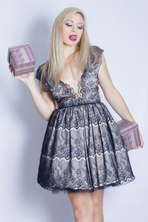 Portrait of a beautiful blonde girl who is holding two gift boxes. Young woman dressed in a beautiful cocktail dress