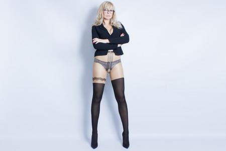섹시 한 비서의 방식으로 섹시 한 금발 소녀의 초상화. 젊은 여자는 검은 자 켓과 검은 색 스타킹을 입고있다. 그녀는 검은 안경을 흰색 배경에있다.