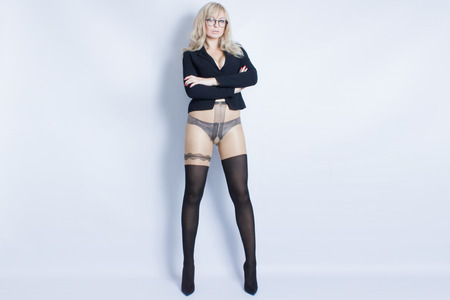 Portrait of a sexy blonde girl in the manner of a sexy secretary. The young woman is wearing a black jacket and black tights. She is on a white background with black glasses