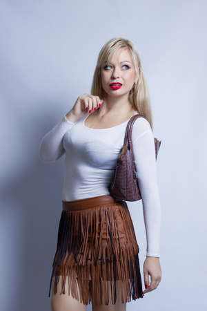 Business portrait of a beautiful young blond woman on a white background. The girl wears a leather brown skirt with a fringe. In her hands a dark brown bag