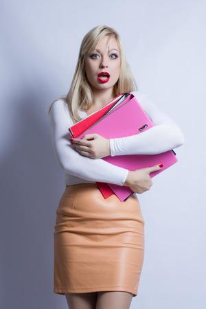 Bedrijfsportret van een mooie jonge blonde vrouw met lang haar. Het meisje is gekleed in een bruin lederen rok en houdt een map vast