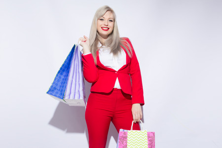 Image of young blonde lady in red costume posing with shopping bags and looking to camera over white background
