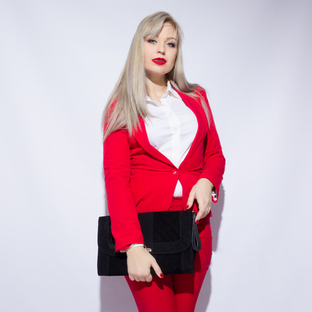 Portrait of a beautiful young blond woman with long hair in a red suit. She holds a big black clutch in her hands  Imagens