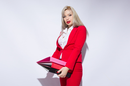 Portrait of a beautiful secretary in a red suit with folders in hands