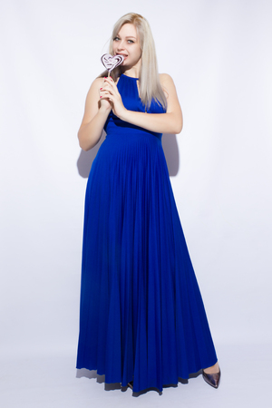 Portrait of a beautiful young blond woman with long hair in blue maxi dress. Girl holding a heart shaped candy